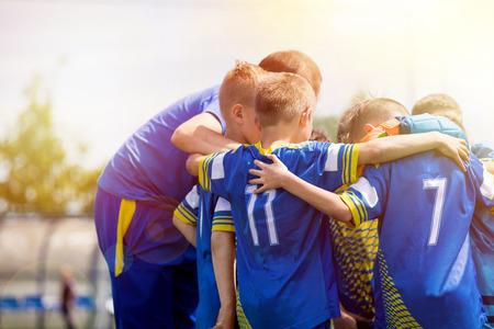 Équipe de sport pour enfants ayant des discussions d'encouragement avec l'entraîneur. Équipe de football d'enfants motivée par un entraîneur. Entraîneur de l'équipe de jeunes de football. Jeunes garçons debout ensemble unis Banque d'images