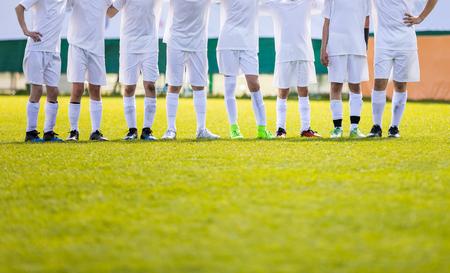 ユースフットボールチーム。若いサッカー選手が列に並んでいます。ペナルティショット中に一緒に立っている男の子。ホワイトサッカージャージーシャツの男の子 写真素材 - 100931324