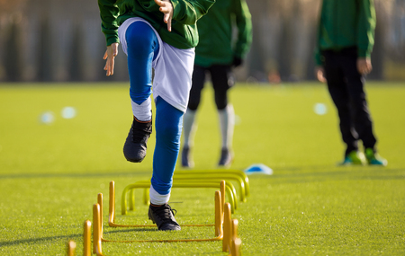 Boy Football Player In Training with Ladder. Young Soccer Players at Training Session. Soccer Speed Ladder Drills Stock Photo