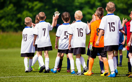 Happy Football Players Giving High Five At Field. Soccer Players High Five After Game. Two Teams High Five After the Weekly Match. Fair Play Rules in Youth Football