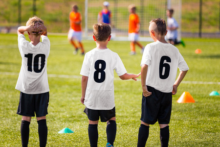 Children Football Team. Young Boys Watching Soccer Match. Football Tournament Competition in the Background. KidsFootball Team Players on Summer Sports Camp