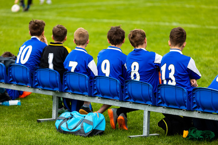 Kids Soccer Team on a Bench. Children Football Team Players. Young Boys in Blue Jerseys as a Substitute Soccer Players. Youth Footballers of Football Club. Sports School Tournament Standard-Bild