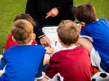 Children Football Team with Coach at the Soccer Field. Kids Coach Explaining The Tactics Board. Boys Listening to Coach's Instructions Before the Sports Tournament Competition