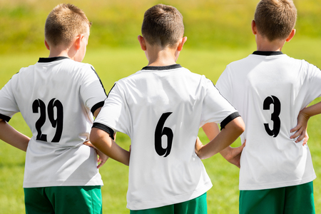 Children Sports Team Wearing White Soccer Jersey Shirts. Young Boys Watching Soccer Match. Football Tournament Competition in the Background. Kids Football Team Players on Summer Sports Camp