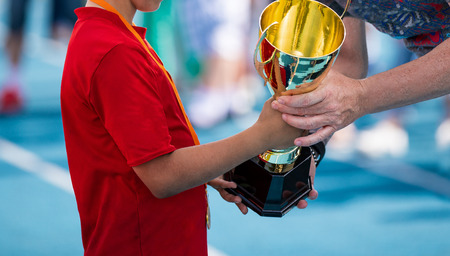 Child in a sportswear receiving a golden cup. Young atlete winning the sports school competition. Boy with golden medal getting an award for the best player of the tournament