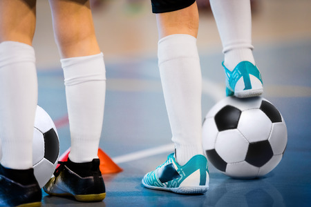 Indoor soccer players training with balls. Indoor soccer sports hall. Football futsal player, ball, futsal floor. Sports background. Futsal league. Indoor football players with classic soccer ball.