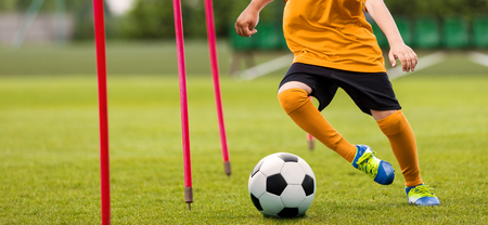 Soccer Player with Soccer Ball Running Slalom Around Training Sticks. Football Speed Training. Young Footballer in Yellow Sportswear at Training Session on Grass Soccer Field Stock Photo