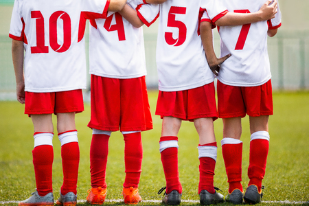 Football children team. Kids soccer substitute players standing together on a row. Football sports tournament for young boys. Four kids watching football penalties game on a pitch Stock Photo