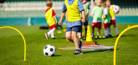 Kid Young Athletes Training with Football Equipment. Football Speed and Agility Training. Young Footballer in Blue Sportswear at Training Session on Grass Soccer Field Фото со стока