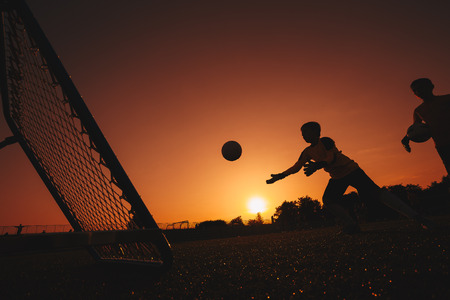 Football Soccer Goalkeeper Training Session. Two Young Goalies Practising in a Field. Soccer Equipment and Ball in the Foreground. Sunset in the Background. Football Training Background Stock Photo