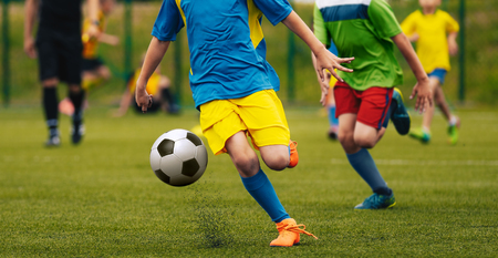 Boys in blue, yellow and green jersey t-shirts kicking football game on the football field. Soccer players running in action. Youth school football match. Soccer referee in the background. Stock Photo
