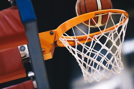 Basketball scoring basket at a sports arena. Scoring the winning points at a basketball game. The orange basketball ball flies through the basket