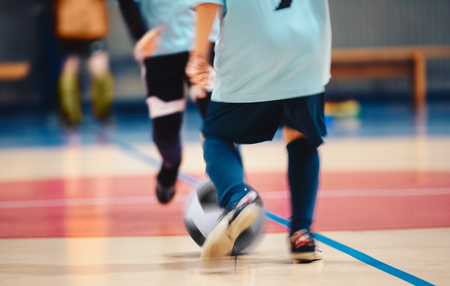 Young futsal players and soccer ball with motion blur. Indoor futsal soccer players in motion playing futsal match. Indoor soccer sports hall. Sport players kicking match. Futsal training dribble