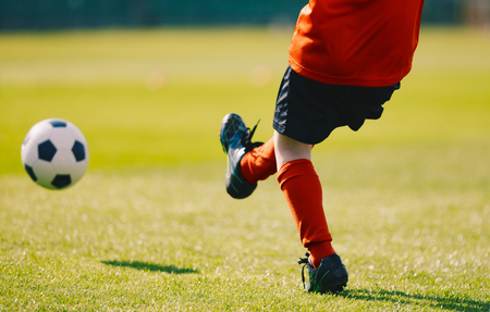 Young Football Player Kicking Ball on the Soccer Pitch. Boy Wearing Red Sports Jersey, Black Shorts, Red Soccer Socks and Black Cleats. Soccer Kick on the Grass Stadium