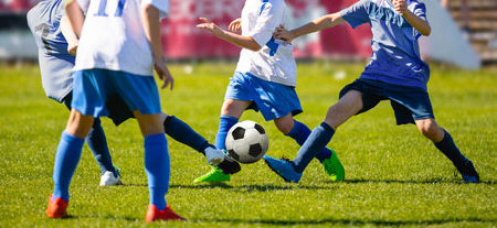 Group of Young Boys in Soccer Sportswear Running and Kicking Ball on the Soccer Grass Field. Low Angle Image of Youth Football Competition with Blurred Stadium Background
