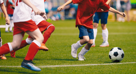 Young Boys in White and Red Soccer Jersey Shirts and Soccer Cleats Kicking Soccer Ball. Football Tournament for Youth Soccer Clubs Academies. School Soccer Competition Stock Photo