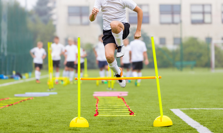 Soccer Player on Fitness Training. Footballers on Practice Session in Field on Sunny Day. Young Soccer Players at Speed and Agility Practice Training Session