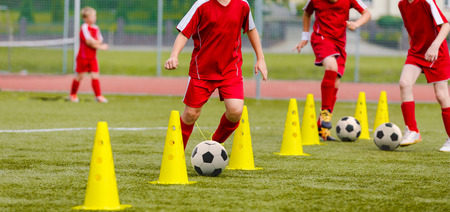 Soccer camp for kids. Boys practice dribbling in a field. Players develop good soccer dribbling skills. Children training with balls and cones. Soccer slalom drills to improve football dribbling pace Stok Fotoğraf