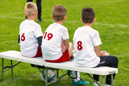 Boys Sitting on Soccer Football Wooden Bench. Kids Football Team. Soccer Tournament Match for Children. Young Boys Playing European Football Game. Children Football Academy. Substitute Soccer Players