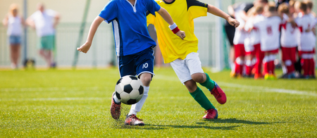Junior Soccer Teams During Running Duel. Football Game For Youth Players. Boys Playing Soccer Match on Football Pitch. Football Stadium and Team Huddling in the Background