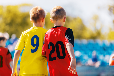 Two Boys Soccer Players in Colorful Jersey Shirts. Kids Children Compete in Sports Competition. Defensive Organization in Junior Youth Football Team