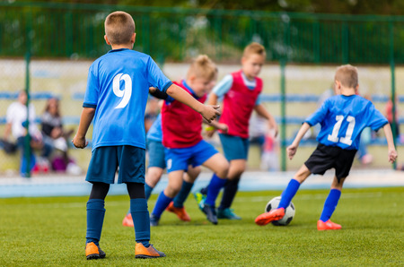 Team of young boys running through green pitch during tournament football match. Children kids having fun playing soccer game outdoor. Soccer season for kids Stock Photo