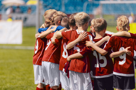 Soccer team huddling. Kids in red sportswear standing together and listening to coach. Junior football soccer tournament match