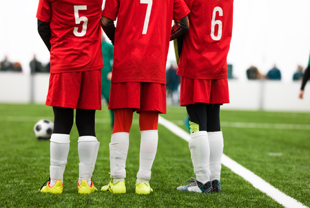 Junior Soccer Players Standing in a Wall. Free Kick Situation During Football Match. Players Wearing Red Soccer Jersey Shirts with Numbers on Back. Soccer Tournament Game Stock Photo