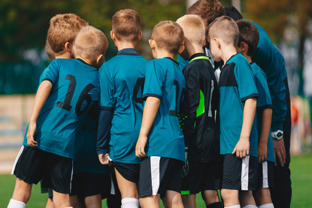 Soccer Boys in Team Huddle. Children On Team Huddle with Football Coach. School Football Team