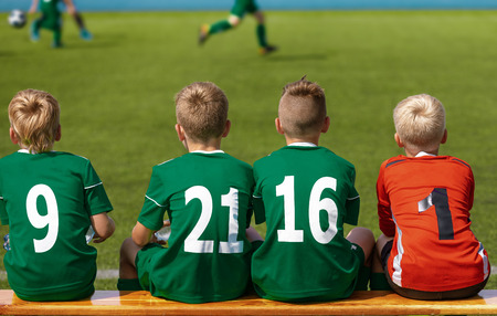 Children Sitting on Soccer Football Wooden Bench. Kids Junior Football Team. Youth Soccer Tournament Match. Young Boys Play European Football Game. Children Football Academy. Substitute Soccer Players
