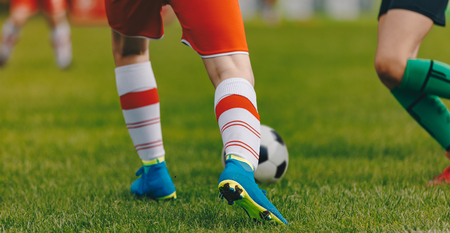 Soccer football kick-off in the stadium. Sporty player running and kicking a soccer ball. Close-up image of football duel