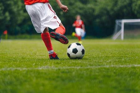 Football Kick on the Field. Player Kicking Soccer Ball