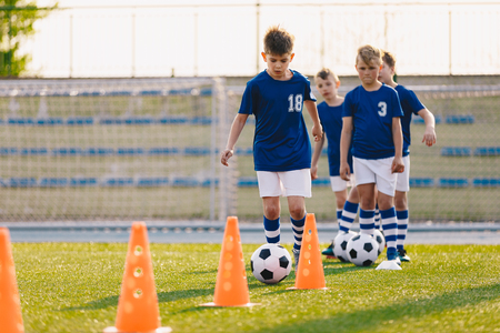 Soccer camp for kids. Boys practice football dribbling in a field. Players develop soccer dribbling skills. Children training with balls and cones. Soccer slalom drills to improve football dribbling pace