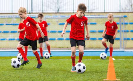 Ragazzi che allenano le abilità di calcio sul campo in erba. Lezione di scuola calcio per bambini