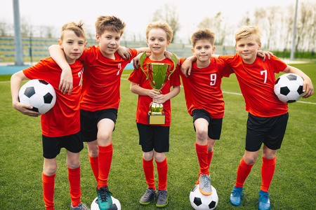 Happy Young Boys In Football Team. Kids in School Soccer Sports Team Holding Golden Trophy and Soccer Balls. Group Of Children In Soccer Team Having Fun After Winning Final Tournament Game