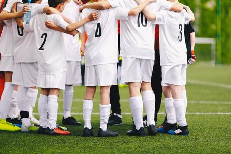 Giocatori adolescenti di calcio di calcio in piedi insieme all'allenatore prima dell'inizio della partita. Discorsi motivazionali dell'allenatore e costruzione dello spirito di squadra degli adolescenti
