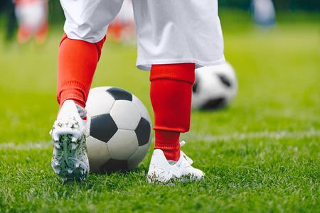 Legs of child in training practice soccer. Kid imprrove dribbling skills on football pitch. Soccer training for children