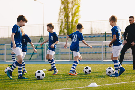 Young Boys in Sports Club on Soccer Football Training. Kids Enhance Soccer Skills on Natural Turf Grass Pitch. Football Practice Session for Children Youth Team of Professional School Soccer Club Stock Photo