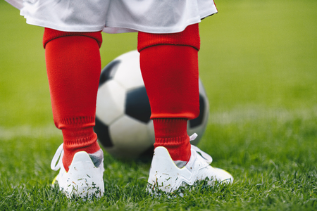 Close up on legs of children soccer player. Young boy kid practice football on grass field Reklamní fotografie