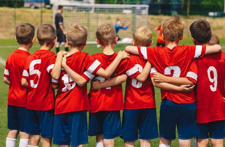Jeugd Europees voetbalteam in rode shirts. Jonge jongens van voetbalclub tijdens de laatste competitie. Kinderen voetbalteam in kruipen op veld. Voetbal penalty shootout