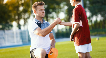 Young Sports Coach Making a High Five with Kids Player. Junior Soccer Coach Coaching Children on Sports Field. Kids Sports Education Outdoor