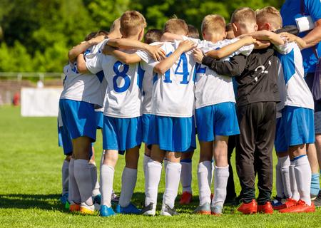 Fußball-Jugendmannschaft, die sich mit Trainer zusammendrängt. Junge glückliche Jungen-Fußballspieler treffen sich vor dem Endspiel