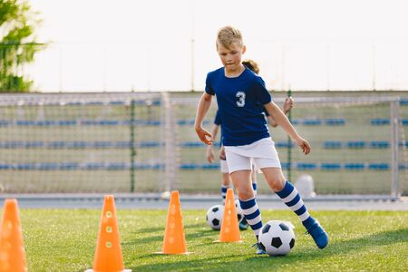 Soccer camp for kids. Boys practice dribbling in a field. Players develop good soccer dribbling skills. Children training with balls and cones. Soccer slalom drills to improve football dribbling pace Reklamní fotografie