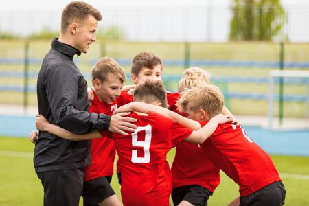 Coaching Youth Sports. Kids Soccer Football Team Huddle with Coach. Children Play Sports Game. Sporty Team United Ready to Play Game. Youth Sports For Children. Boys in Sports Jersey Red Shirts Banco de Imagens