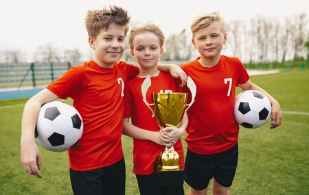 Happy Sports Soccer Team Players Holding Trophy. Winners of Youth Football Tournament