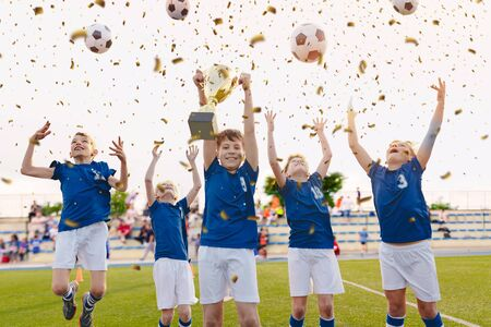 Happy Boys Celebrating Soccer Championship. Youth Football Winning Team Jumping and Rising Golden Cup on Trophy Ceremony After the Final Tournament Game. Football Stadium and Fans in the Background Stockfoto