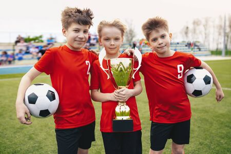 Three Happy Cheerful Kids of Sports Soccer Team. Boys Football Players Holding Trophy at the Stadium. Young Winners of Youth Football Tournament
