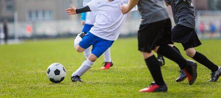 Torneo de Fútbol para Academias de Clubes de Fútbol Juvenil. Competición Deportiva Escolar. Cuatro niños con camisetas de fútbol blancas y negras y botines de fútbol pateando una pelota de fútbol clásica Foto de archivo
