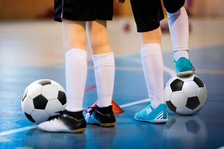 Futsal soccer training. Two young futsal players with balls on training. Close up of legs of futsal footballers