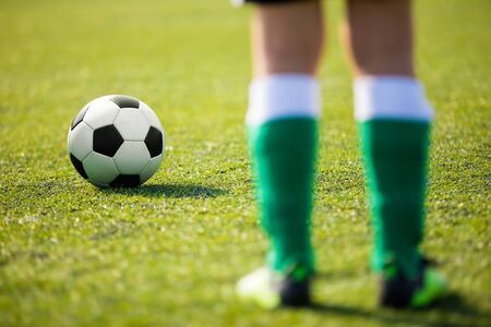 One soccer football player standing next to ball ready to kick. Legs of junior level football player an classic soccer ball Stock Photo